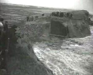 Naar omstandigheden nog netjes gericht liggen de zandzakken in de tuinen ingebed om de golven een halt toe te roepen