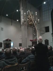 Terwijl het publiek op het koor wacht worden de kaarsen ontstoken