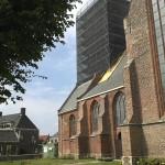 De zuidelijke gevel van de Ouder Kerk met de toren in de steigers.